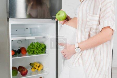 Foto de Vista cruzada de la mujer embarazada que tiene manzana cerca de la nevera abierta con verduras y frutas frescas. - Imagen libre de derechos
