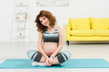 Photo pour Attractive pregnant woman in sportswear smiling at camera while sitting on fitness mat in living room - image libre de droit