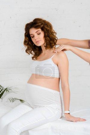 Photo pour Masseur faisant massage du dos à la belle femme enceinte sur la table de massage au centre de spa - image libre de droit