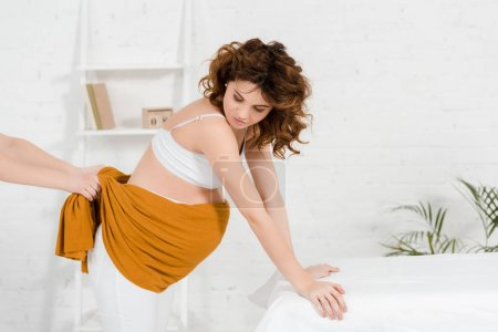 Photo pour Vue latérale de la femme enceinte pendant le massage du ventre avec chiffon dans le centre de spa - image libre de droit