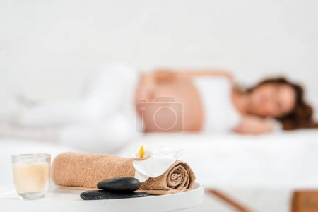 Photo pour Concentration sélective de pierres, bougie avec serviette et orchidée sur table avec femme enceinte sur table de massage au centre de spa - image libre de droit