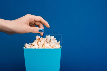 Photo for Cropped view of woman taking popcorn isolated on blue - Royalty Free Image