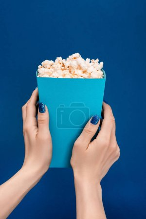 Photo pour Cropping view of woman holding box with popcorn isolated on blue - image libre de droit