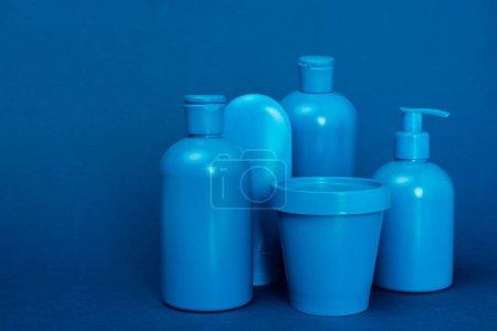 Photo pour Bouteilles avec après-shampooing, gel douche, savon liquide et seau sur fond bleu - image libre de droit