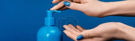 Photo for Panoramic shot of woman pumping out liquid soap isolated on blue - Royalty Free Image