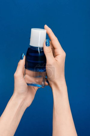 Photo pour Cropped view of woman holding micellar cleansing water isolated on blue - image libre de droit