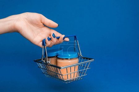 Photo for Cropped view of woman holding shopping basket with baby food in jars on blue background - Royalty Free Image