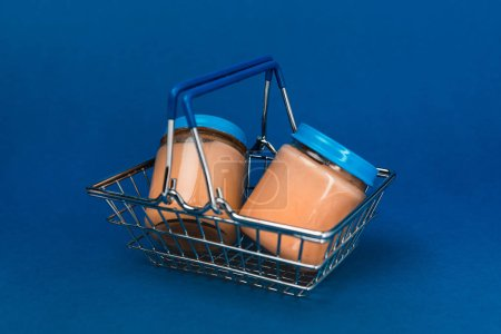 Photo for Jars with baby food in shopping basket on blue background - Royalty Free Image