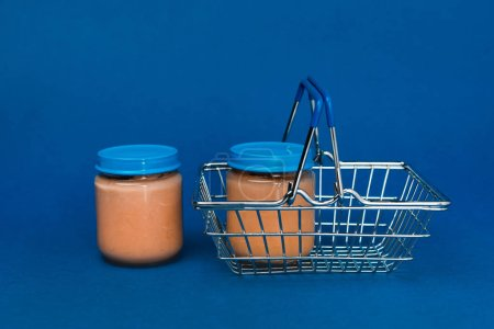 Photo for Jars with baby food and shopping basket on blue background - Royalty Free Image