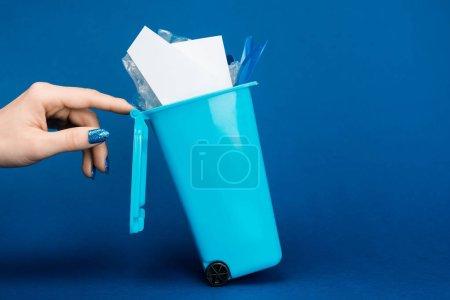 Foto de La vista recortada de la mujer que toca la basura de juguete puede en el fondo azul. - Imagen libre de derechos