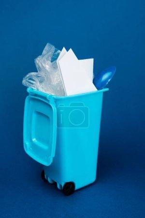 Photo pour Boîte à ordures de jouets avec déchets sur fond bleu - image libre de droit