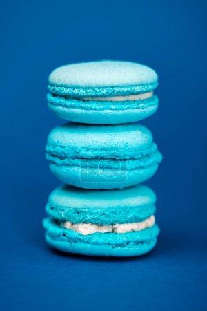 Photo pour Macarons français sucrés et savoureux sur fond bleu - image libre de droit