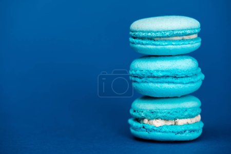 Photo for Tasty french macaroons on blue background with copy space - Royalty Free Image