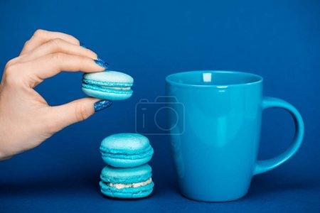 vista recortada de la mujer sosteniendo macarrón francés cerca de la taza sobre fondo azul