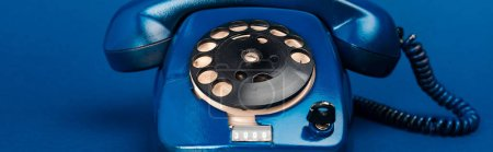 Foto de Foto panorámica del teléfono retro en fondo azul - Imagen libre de derechos