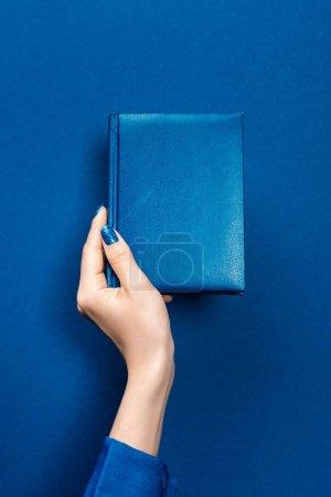 Photo pour Vue recadrée d'une femme tenant un carnet sur fond bleu - image libre de droit