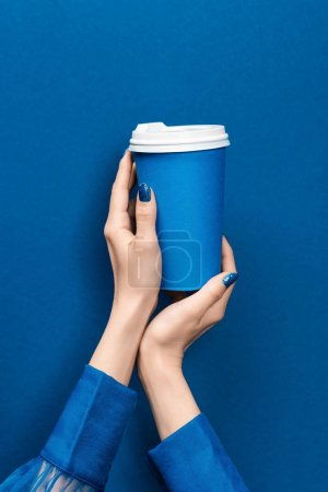 cropped view of woman holding paper cup on blue background