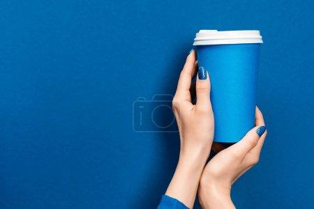 Photo pour Vue recadrée de la femme tenant tasse en papier sur fond bleu - image libre de droit