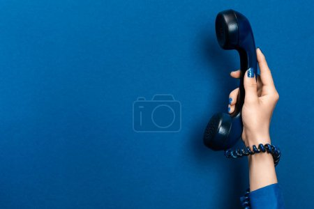 Photo for Cropped view of woman holding handset on blue background - Royalty Free Image