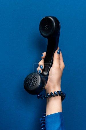 Photo pour Vue recadrée de femme tenant combiné sur fond bleu - image libre de droit