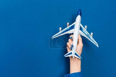 Photo pour Vue recadrée de la femme tenant modèle de plan sur fond bleu - image libre de droit