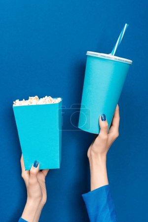 Photo pour Vue recadrée de la femme tenant pop-corn et tasse en papier sur fond bleu - image libre de droit