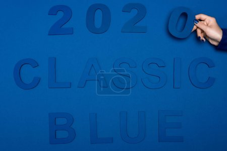Photo for Cropped view of woman holding number near classic blue lettering on blue background - Royalty Free Image