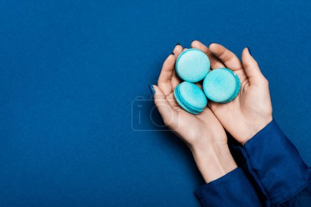 Photo for Cropped view of woman holding french macaroons on blue background - Royalty Free Image