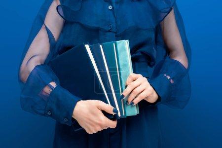 Photo pour Vue recadrée de femme tenant des livres sur fond bleu - image libre de droit