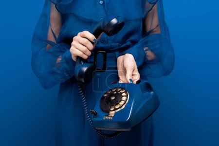 Foto de Vista recortada de la mujer que tiene teléfono retro sobre fondo azul - Imagen libre de derechos