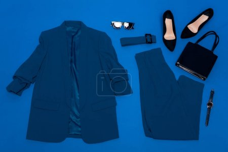 Photo pour Vue de dessus de veste, pantalon, talons, ceinture, sac, montre-bracelet et lunettes de soleil isolés sur bleu - image libre de droit