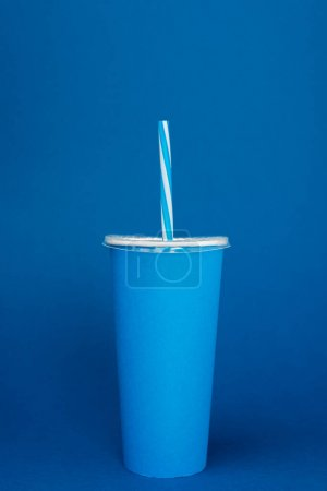paper cup with plastic straw on blue background