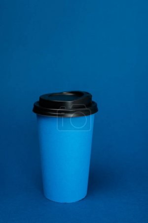 paper cups with coffee on classic blue background with copy space