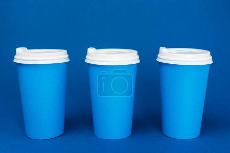 Photo pour Tasses en papier avec café sur fond bleu classique - image libre de droit