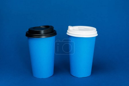 paper cups with coffee on classic blue background