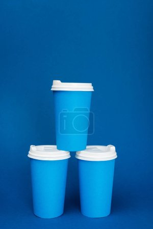 paper cups with coffee on blue background with copy space