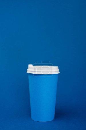 Photo pour Tasse en papier avec café sur fond bleu avec espace de copie - image libre de droit