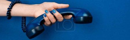 Photo pour Plan panoramique de femme tenant combiné sur fond bleu - image libre de droit