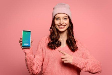 Photo pour KYIV, UKRAINE - 29 NOVEMBRE 2019 : joyeuse fille pointant du doigt son smartphone avec application Twitter à l'écran isolé sur rose - image libre de droit