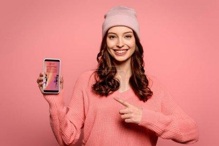 Photo pour Heureuse fille pointant du doigt le smartphone avec la meilleure application shopping à l'écran isolé sur rose - image libre de droit