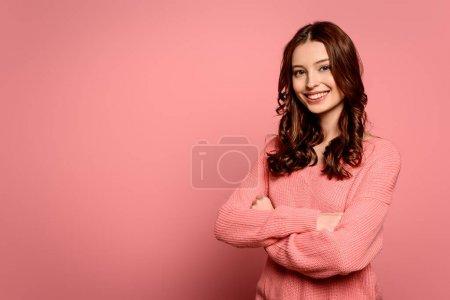 Photo pour Fille gaie regardant la caméra tout en se tenant avec les bras croisés sur fond rose - image libre de droit