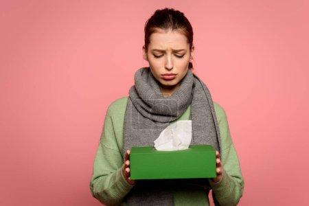 Photo pour Triste, fille malade en écharpe chaude prenant boîte de serviettes en papier isolé sur rose - image libre de droit