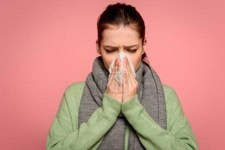 Photo pour Malade fille dans chaud éternuement écharpe en papier serviette isolé sur rose - image libre de droit