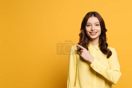 lächelndes Mädchen zeigt mit dem Finger in die Kamera auf gelbem Hintergrund