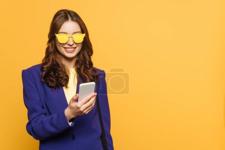 Photo for Cheerful, stylish girl in yellow glasses chatting on smartphone isolated on yellow - Royalty Free Image