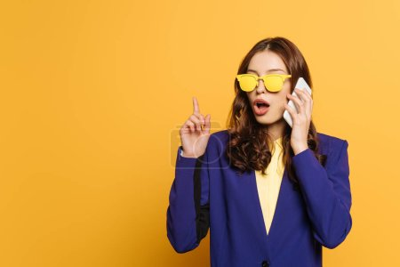 Photo for Amazed, stylish girl in yellow glasses showing idea sign while talking on smartphone isolated on yellow - Royalty Free Image