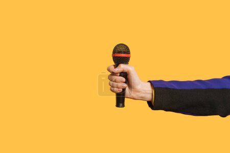 cropped view of reporter holding microphone isolated on yellow