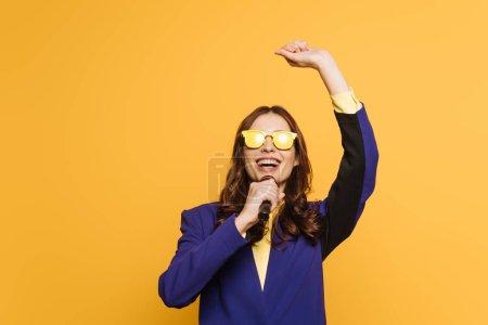 Photo pour Jeune chanteur en verres jaunes chantant avec la main levée isolé sur jaune - image libre de droit