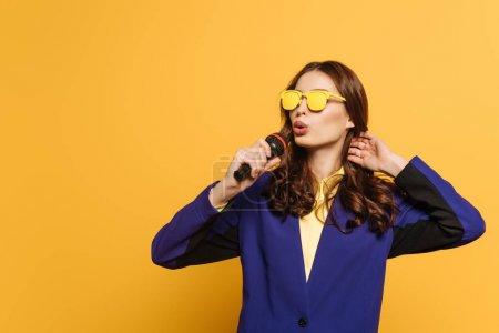 Photo pour Belle chanteuse en verres jaunes chantant avec microphone sur fond jaune - image libre de droit