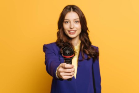 Photo pour Selective focus of journalist holding microphone on yellow background - image libre de droit